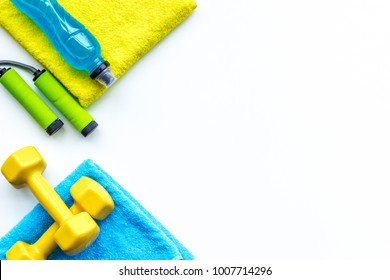 Do fintess in gym. Dumbbells, jump rope, mat, water on white background top view space for text pattern
