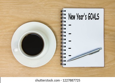 To do list 2019 goals paper book and hot coffee cup on wood background.  New Year's Resolution 2019 on book and wooden background.  target success concept. top view.