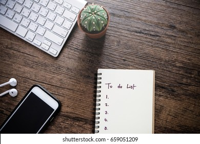 To do list by priority in note book beside are smart phone,keyboard,cactus and small talk on wooden table, business concept
