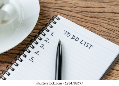 To Do List concept, pen on white paper note pad with handwritten headline as To Do List and numbers listed with coffee cup on wood table, writing business project with tasks priority.