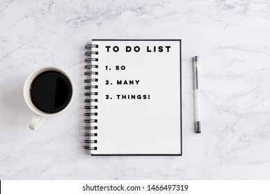 To do list so many things writing on notebook. Notebook on desk with coffee cup and a pen.