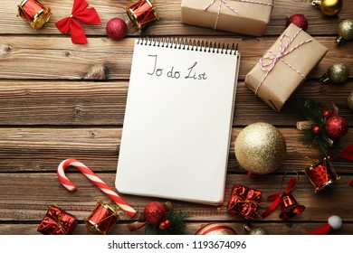 to do list in notepad with christmas decorations on wooden table - Christmas Decorations List