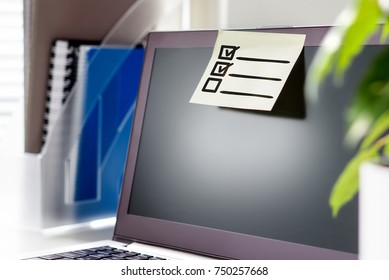 To do list in office. Planning and organizing concept. Checklist of tasks and agenda for work day. Sticky paper and post it note on laptop in workstation.