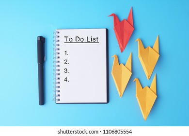 To Do List with origami on blue background