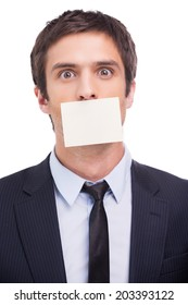 To do list. Portrait of frustrated young man in formalwear and adhesive note on his mouth standing against white background and looking at camera