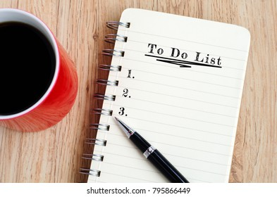 To do list text on notepad with pen and a cup of coffee, wooden background