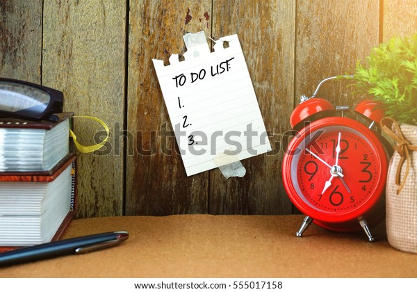 TO DO LIST text written on sticky note. Books, pen, spectacle and red clock on brown desk. Education and business concept.