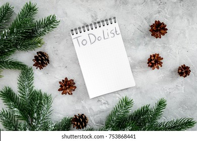 To do list for winter shopping at notebook near spruce branch and pinecones on grey stone background top view.