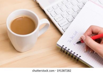 """Liste erstellen. Frau schreibt an ihrem Schreibtisch eine """"To-Do-Liste"""" mit einer Tasse frischen Kaffee"""