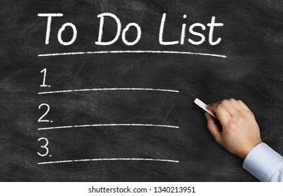 To Do List written on the blackboard with hand holding white chalk