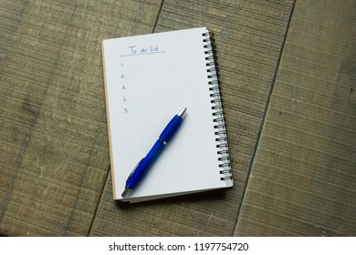 To do list written on a spiral blocknote with a blue pen on a wooden background