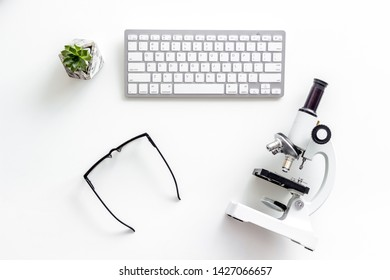 Do medical research on laboratory desk with microscope, keyboard, glasses on white background top view