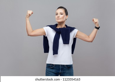 Do no mess with powerful and confident woman. Pleased self-assured strong adult woman nodding to assure, raising hands with clenched fists showing muscles standing over gray background. isolated shot