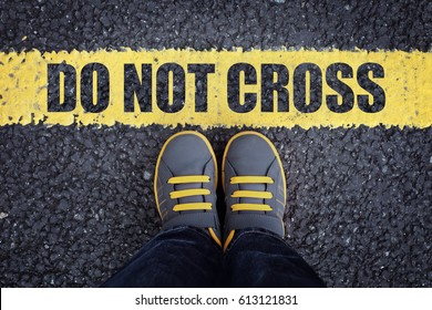 Do not cross line child in sneakers standing next to a yellow line with restriction or safety warning