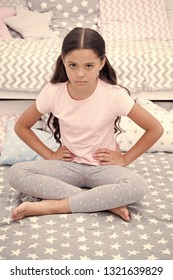 Do not disturb child before sleep. Girl child sit on bed in her bedroom. Kid unhappy someone entered her bedroom bothering her. Girl kid long hair cute pajamas serious unhappy face. Get out of here.