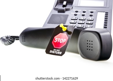 Do not disturb label with a thumbtack and office phone with a phone tube. Do not disturb with your calls concept. Isolated on white.