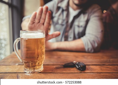 Do not drink and drive! Cropped image of man showing stop gesture and refusing to drink beer. Car keys lying near