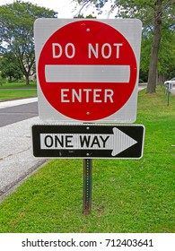 A Do Not Enter and One Way Sign Next to A Road Directing Traffic