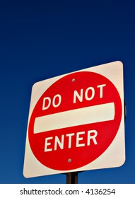 A Do Not Enter road sign against a deep blue sky