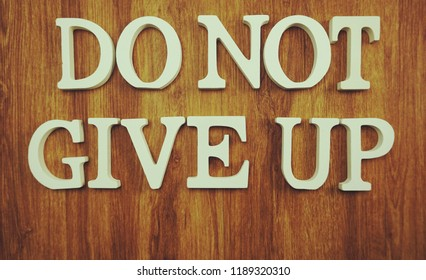 do not give up letters alphabet on woodden background