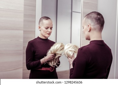 Do not like it. Pessimistic girl bowing head while looking at wig