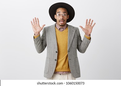 Do not look at me, it was not my fault. Portrait of unaware worried guy in stylish jacket and hat raising palms in surrender gesture, anxious while trying explain his innocence over gray background