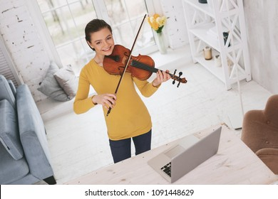 Do not lose your melody. Happy young female using her violin while playing classical melody