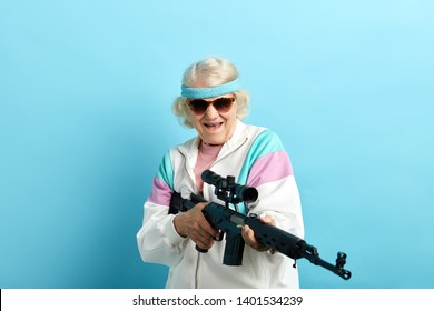 Do not make your grandmother angry. Grandma can respond. Comic portrait of old-aged grandma in whiye sportive outfit and dark sunglasses holding sniper rifle, pointing aside over blue background