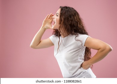 Do not miss. Young casual woman shouting. Shout. Crying emotional woman screaming on pink studio background. Female half-length profile portrait. Human emotions, facial expression concept. Trendy