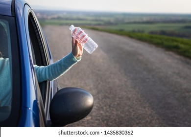 Do not pollute environment with plastic ! Driver hand holding plastic bottle from car window. Environmental conservation.