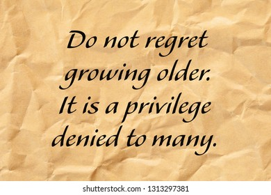 Do not regret growing older. It is a privilege denied to many. Positive aging quote written on crumpled brown paper.