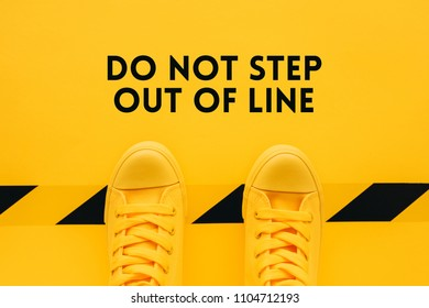 Do not step out of line, person in yellow sneakers breaking the rules and acting in an inappropriate or unacceptable way