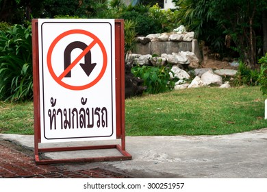 Do not U-turn sign steel stand on the road in front of lawn.