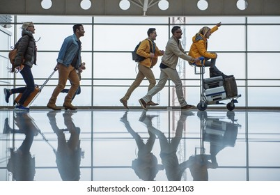 Do not want to be late. Full length profile of joyful young friends are running along terminal hall with suitcases. Male is pushing airport trolley with luggage and female who is sitting on it