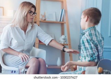 Do not worry honey. Female psychotherapist reaching out to a male youngster while both chatting over anxiety and worries of the boy.