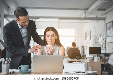 Do not worry. Serene male talking with crying lady. She having job with laptop in office. Support during trouble concept