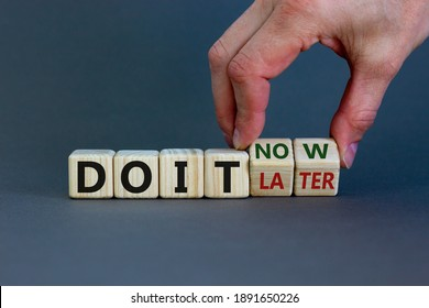 Do it now symbol. Businessman hand turns cubes and changes words 'do it later' to 'do it now'. Beautiful grey background. Business and do it now concept. Copy space.