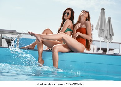 Do something cool with your summer. Girls sitting by the pool, splashing the water and laughing