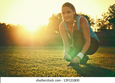 Do Sport in the sunset / Young woman preparing to run in a playground, sunset in the background