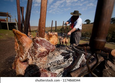 Cambará do Sul, Rio Grande do Sul / Brazil - 08/02/2015: Barbecue ribs prepared in gaucho way, with wood on the ground and meat on the stick