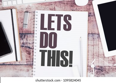 Let's do this!!! Motivational message overhead view of workspace with keyboard, tablet, smart phone and cup of tea with copy space