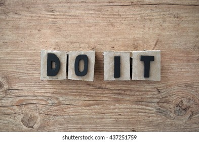 Do it wrote in raw cardboard alphabet stamp in wood background. Rustic alphabet stamp with black letters.
