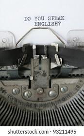 'do you speak English' written on an old typewriter, detail vertical photo.
