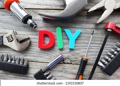 Do it yourself concept with DIY acronym from plastic letters in the middle of tools prepared for work