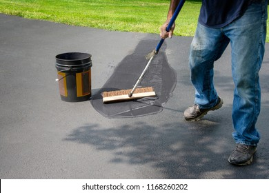 Do it yourself home maintenance. Driveway resealing repair. Homeowner spreads blacktop sealant.