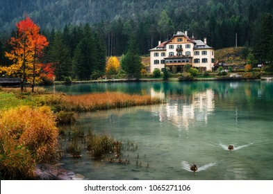 Dobbiaco Lake or Toblacher in Dolomites with hotel restaurant on coast in autumn