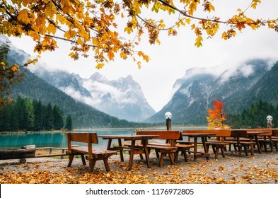 Dobbiaco Lake or Toblacher in Dolomites with wooden tables and benches in outdoor cafe restaurant in autumn