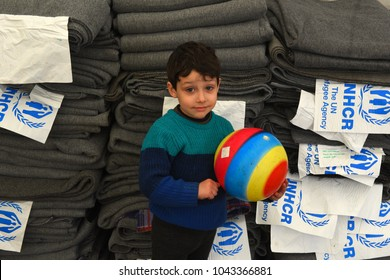 Dobova, Slovenia - 4 february 2016: Little boy in refugee camp holding a colorful ball standing in front of a pile of grey duvets with UNHCR signs.