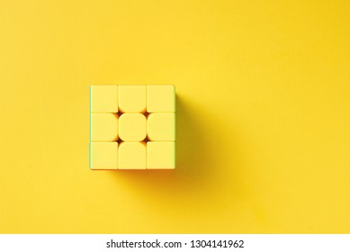 Dobrush, Belarus - 3 February 2019. Rubics cube on yellow background, top view