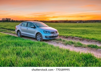 Dobrush, Belarus - May 27, 2017: Dramatic fire sky at sunset and car Volkswagen Polo Vento in a field with green grass on a rural road